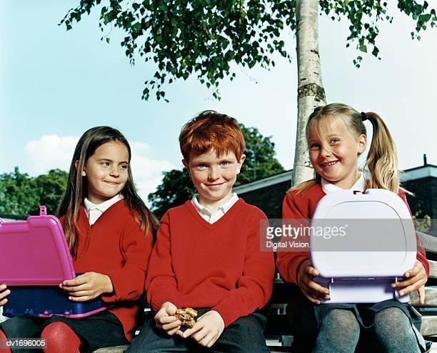 Schoolboy Sitting Between Schoolgirls Eating Their Packed Lunch at School