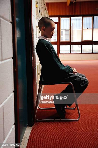 Schoolboy (8-10) sitting on chair by door in corridor, side view