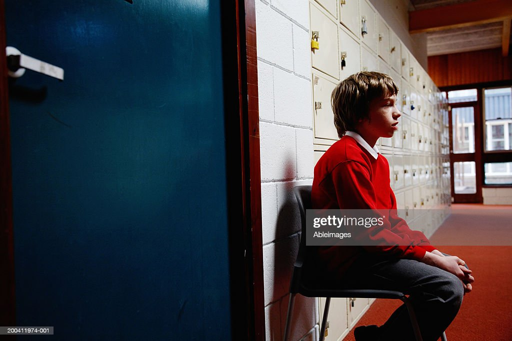 Schoolboy (11-13) sitting on chair in corridor, side view : Stock Photo