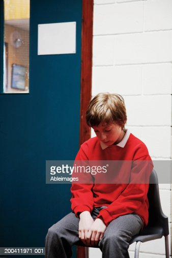 Schoolboy (11-13) sitting on chair outside classroom, head bowed