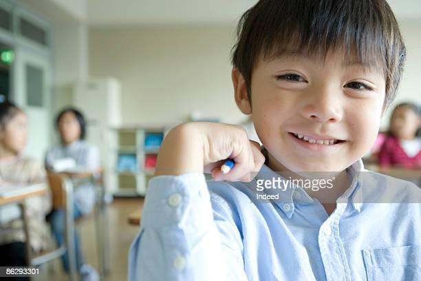 Schoolboy (6-7) smiling in classroom, portrait