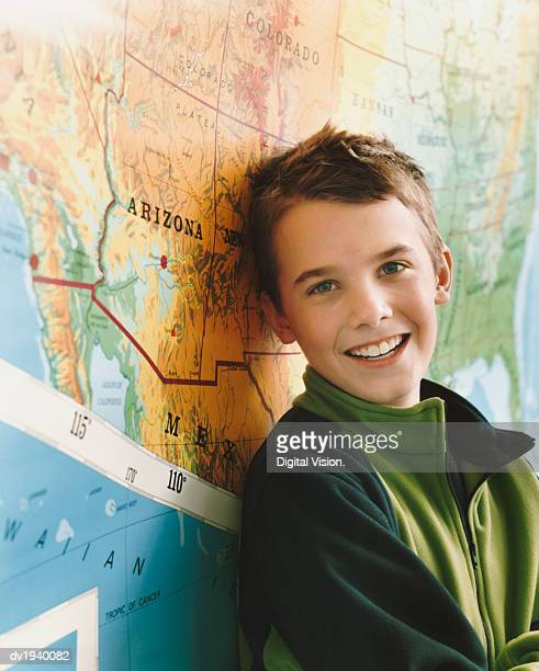 Schoolboy Standing by a Map of the USA in a Classroom