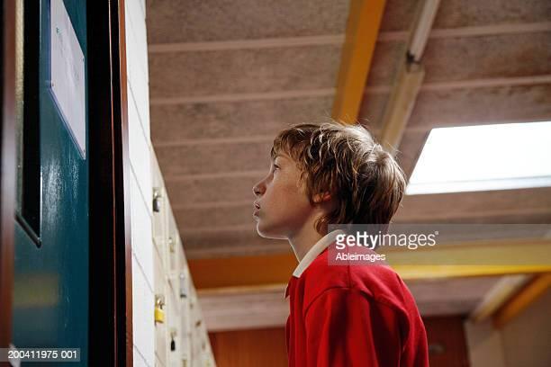 Écolier garçon (du 11 au 13) debout à l'extérieur de l'hôtel, Vue en contre-plongée