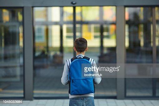 Schuljunge steht vor der Tür der Schule : Stock-Foto