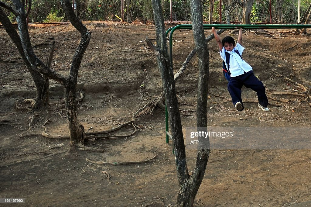 A schoolboy swings from a children's game in the yard of the Jean Paul Genie primary school during the year's first day of classes, in Managua, on February 11, 2013. AFP PHOTO/Hector RETAMAL