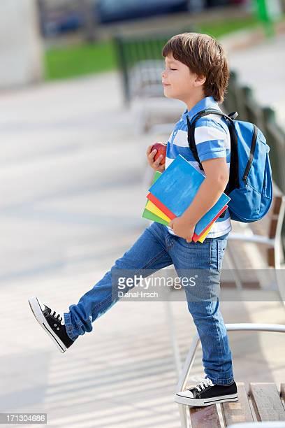 Écolier garçon en essayant de sauter avec les yeux fermés