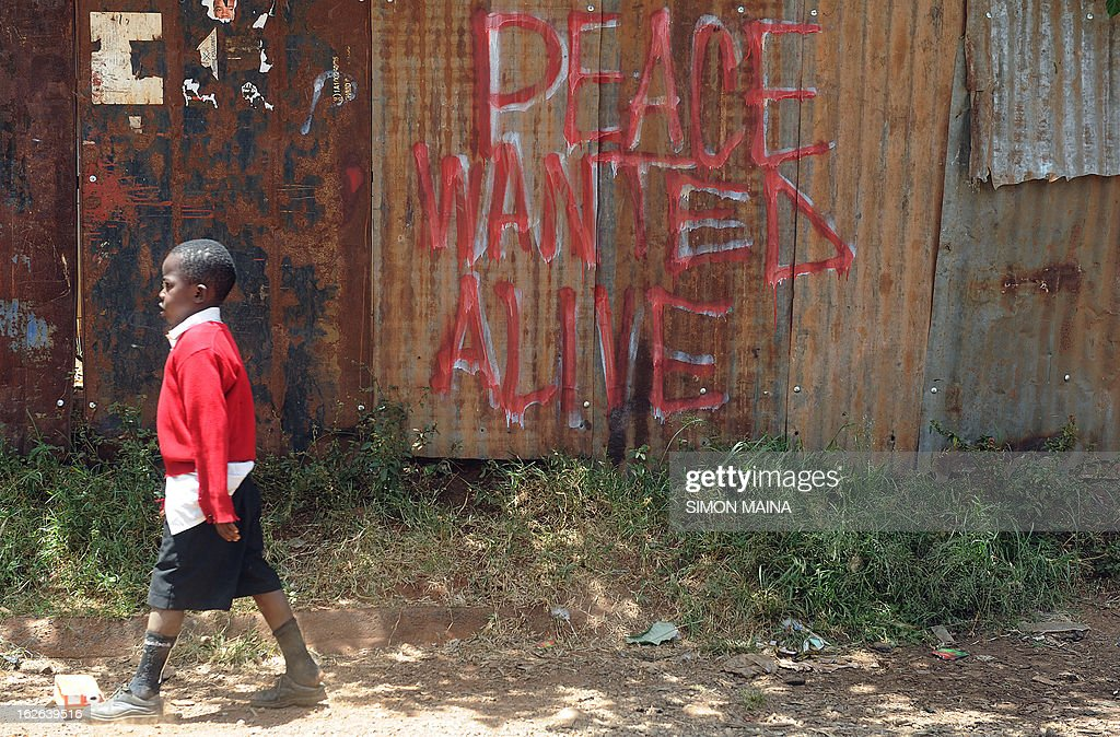 A schoolboy walks past a peace message urging peaceful polls on February,25, 2013 in the sprawling Kibera slums. Kenya is gearing up for presidential, gubernatorial, senatorial elections on March 4, the first since bloody post-poll violence five years ago in which more than 1,100 people died after contested results. AFP PHOTO/SIMON MAINA