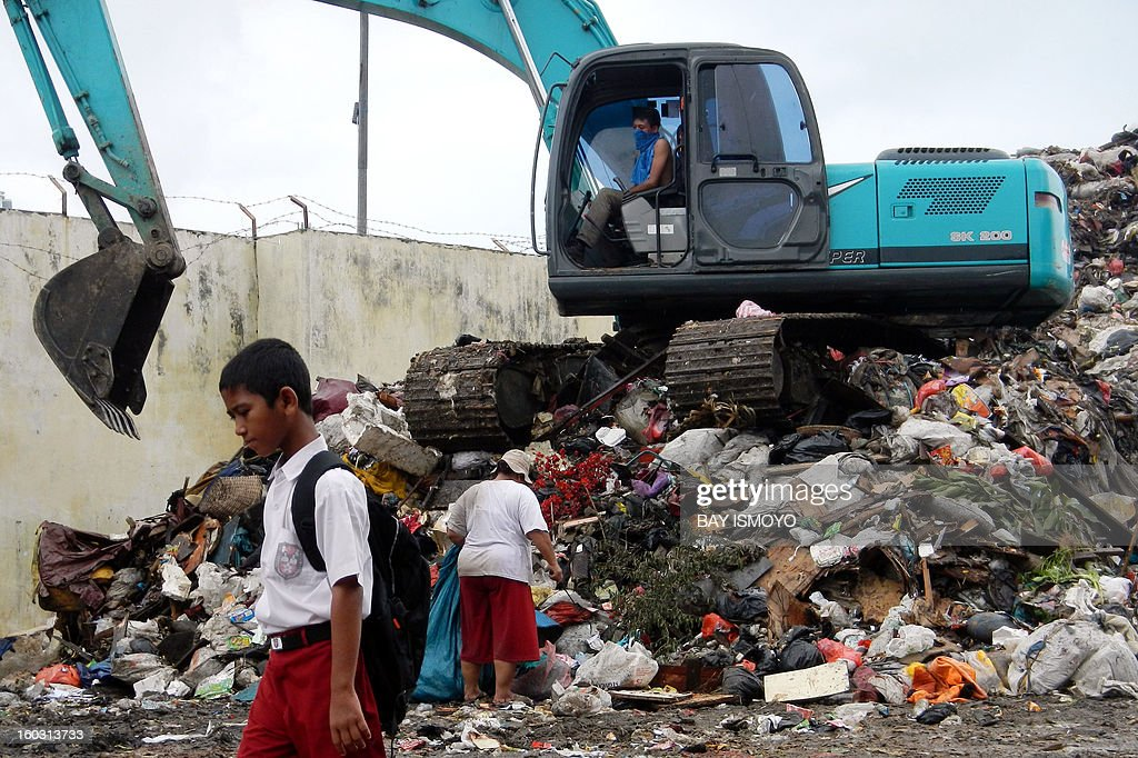 A schoolboy (L) walks past as a 'scavanger' (back R) looks through searches rubbish for valuable items at a garbage dump in Jakarta on January 29, 2013. Indonesia's National Development Planning Board (BPPN) showed the poverty rate in villages and cities in September 2011 was 12.36 percent compared to September 2012, when the figure was further reduced to 11.66 percent, slightly below the target of 11.5 percent. The government is aiming in 2013 to reduce poverty to as low as 9.5 percent. AFP PHOTO / Bay ISMOYO