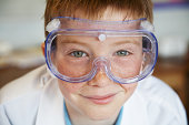 Schoolboy (11-13) wearing protective goggles, smiling, portrait