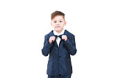 Adorable handsome boy posing in formal kids suit holding a bowtie and looking at camera, Isolated on white background