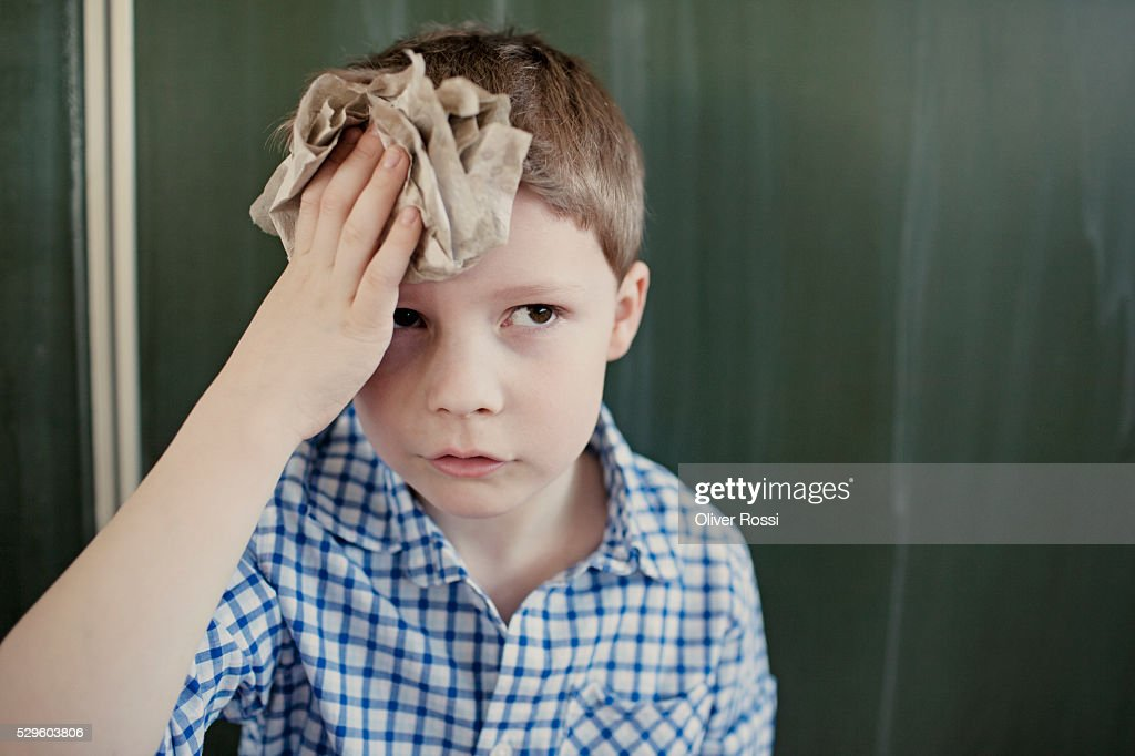Schoolboy (8-9) wiping his forehead with paper towel : Stock Photo
