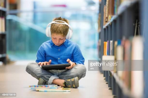 Niño en edad escolar con auriculares y tableta digital sentado en la biblioteca piso