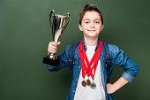 schoolboy with medals holding winner cup near blackboard