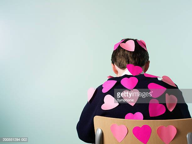 Schoolboy (12-13) with paper heart on back, rear view