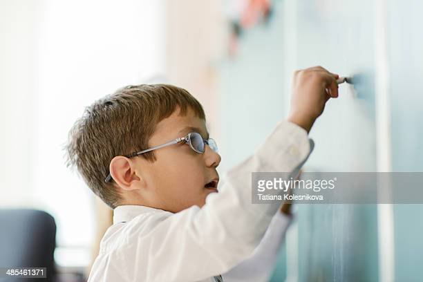 Schoolboy writing on chalk board