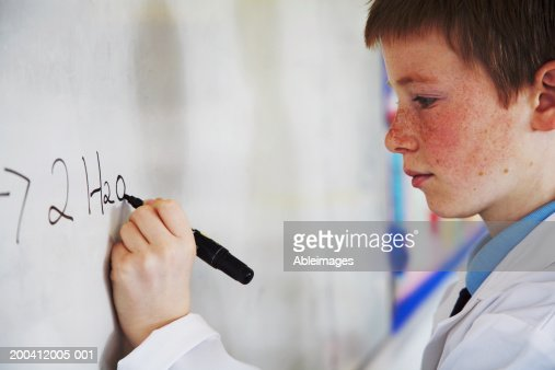 Schoolboy (11-13) writing on whiteboard in class, side view, close-up : Stock Photo