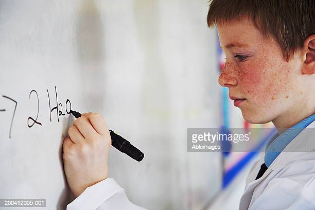 Schoolboy (11-13) writing on whiteboard in class, side view, close-up