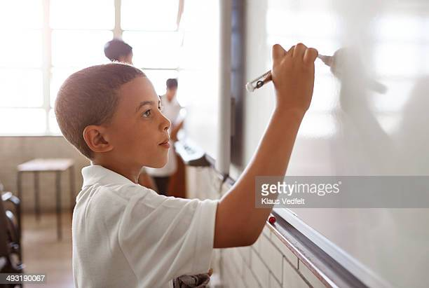 Schoolboy writing on whiteboard