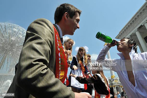 Schoolboys and schoolgirls drink champagne in a fountain during a traditional gathering of school graduates on Independence Square in Kiev on May 29...