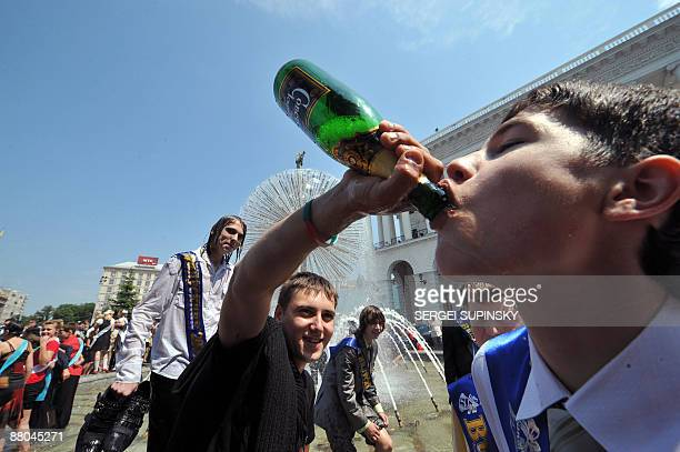 Schoolboys drink champagne in a fountain during a traditional gathering of school graduates on Independence Square in Kiev on May 29 2009 Some 704000...
