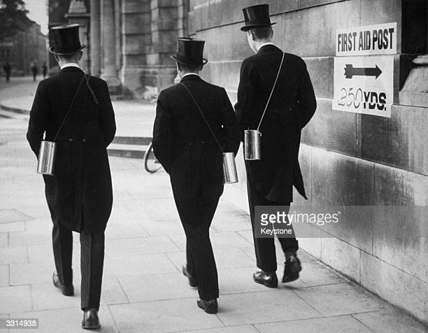 Schoolboys from Eton wearing their gas masks in the 'post office messenger' type of carrier
