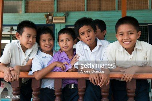 Schoolboys having break on porch of their school.