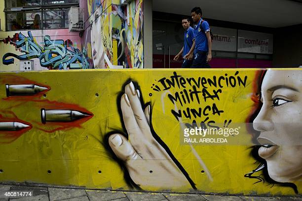 Schoolboys walk next to a graffiti reading 'Military intervention never more' at the 13 Commune shantytown in Medellin Antioquia department Colombia...