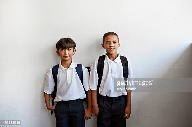 Schoolboys with uniforms standing against wall