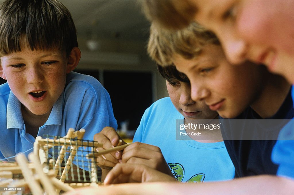 Schoolboys (7-9) working with construction model in classroom : Stock Photo