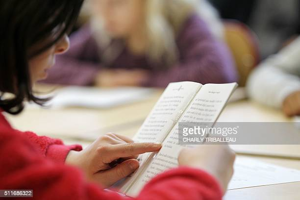 A schoolchild reads a book in a classroom during a visit of French National Education minister on February 22 2016 in Le Havre northwestern France /...