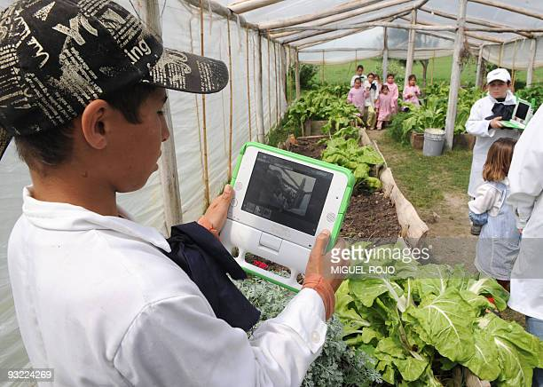 A schoolchild takes measures with his laptop in the greenhouse of a rural school in Rincon de Vignoli department of Florida some 80 km north of...