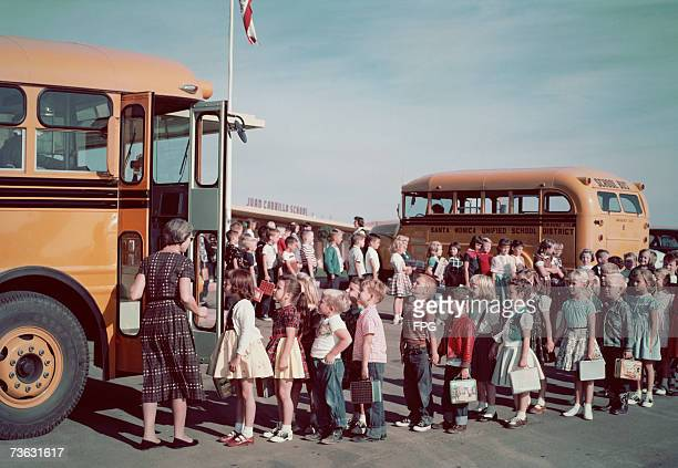 Schoolchilden queueing in pairs to get on the school bus circa 1960