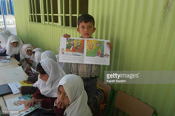 Schoolchildren attending a makeshift classroom outside their ruined school awaiting reconstruction almost a year after a major earthquake struck the...
