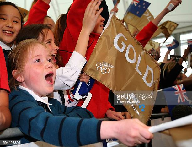 Schoolchildren cheer the athletes onto the stage during the New Zealand Olympic Games athlete home coming at Auckland International Airport [OR] The...