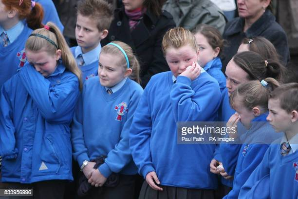 Schoolchildren from the local school who formed a guard of honour as the seven coffins of the McElhill family are removed for burial after requiem...