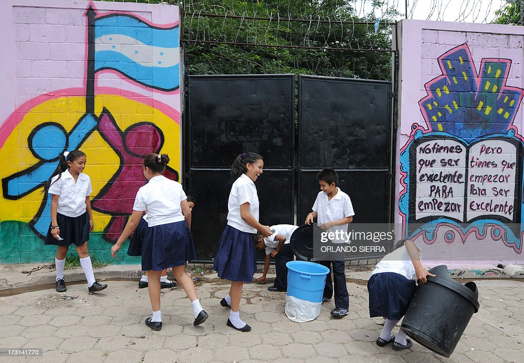 Schoolchildren help clean learning facilities and sidewalks during a Health Ministry campaign focused on mosquito control in order to combat dengue fever, a disease caused by four strains of virus that are spread by the mosquito Aedes aegypti, in Tegucigalpa on July 8, 2013. Authorities have issued dengue alerts in four nations across Central America, where alarm is rising as the mosquito-borne disease has infected 30,000 people and killed 17 this year alone. The illness can be fatal, developing into hemorrhagic fever, which can lead to shock and internal bleeding. AFP PHOTO / Orlando SIERRA