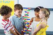 Cute schoolchildren holding DNA model in classroom