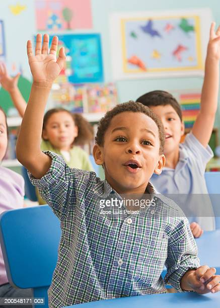 Schoolchildren (2-7) in the classroom, hand raised