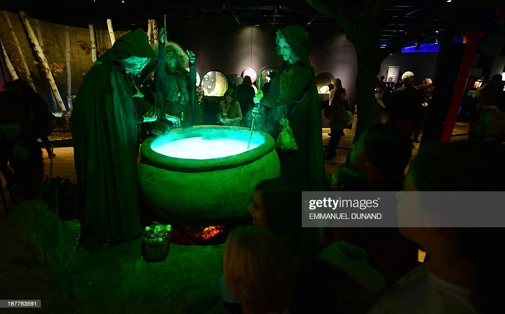 Schoolchildren look at three witches stiring a potion in a cauldron during a preview of 'The Power of Poison' exhibition at the American Museum of...