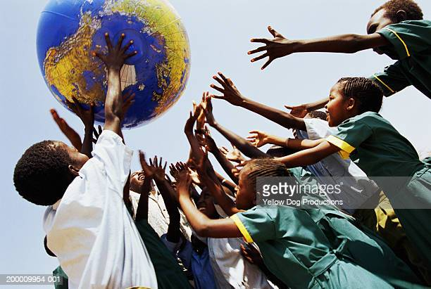 Schoolchildren (8-12) playing with inflatable globe