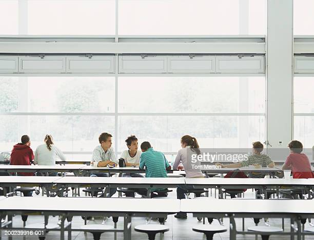 Schoolchildren (12-16) sitting at tables in canteen
