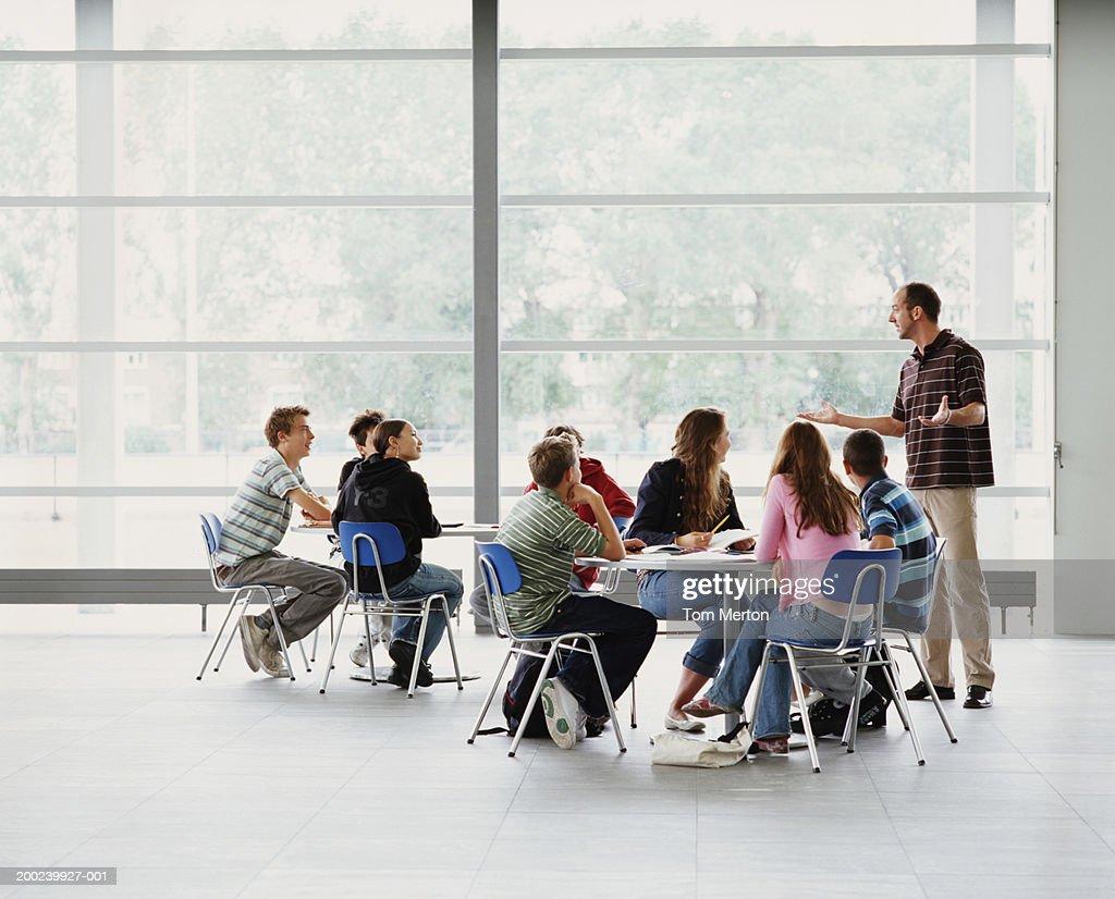Schoolchildren (12-16) sitting at two tables having seminar