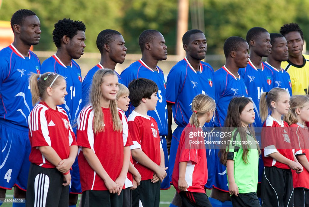 Schoolchildren stand with the Haitian National Soccer team ...