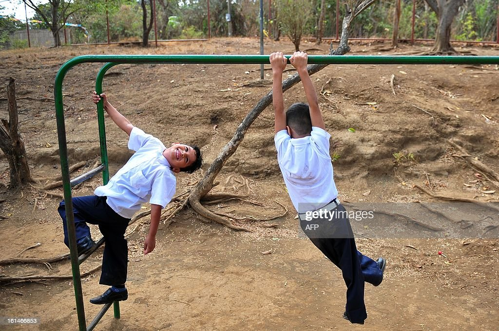 Schoolchildren swing from a game in the yard of the Jean Paul Genie primary school during the year's first day of classes, in Managua, on February 11, 2013. AFP PHOTO/Hector RETAMAL