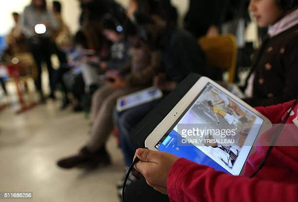 Schoolchildren use digital tablets in a classroom during a visit of French National Education minister on February 22 2016 in Le Havre northwestern...