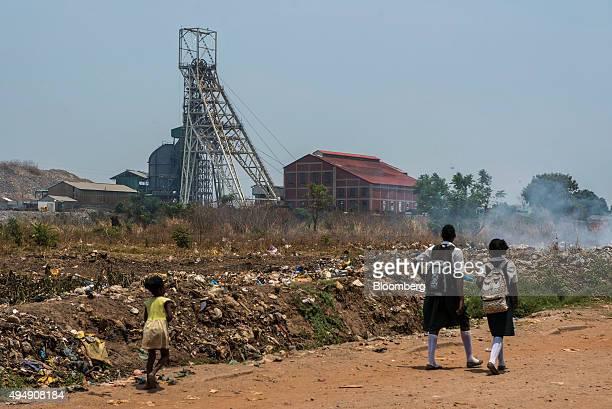 Schoolchildren walk past a field strewn with smouldering garbage near the South Ore Body Shaft at the Mopani copper mine a Zambian unit of Glencore...