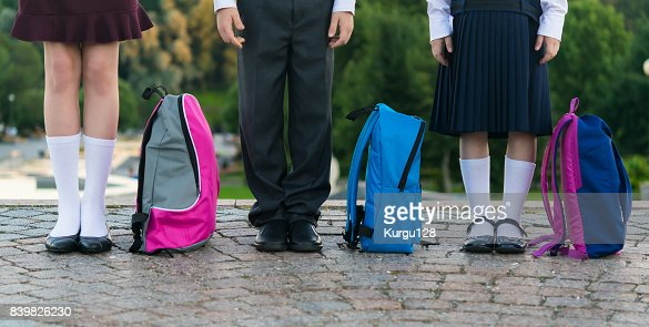 Schoolchildren with backpacks stand in the park ready to go to school, long photo : Stock Photo
