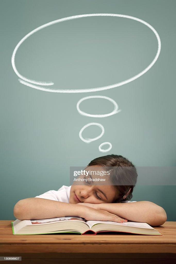 Schoolgirl asleep at her desk : Stock Photo