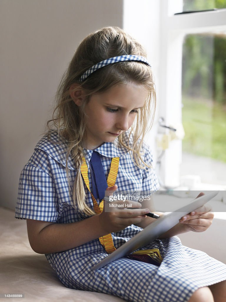 Schoolgirl at home on tablet : Stock Photo