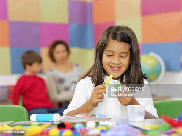 Schoolgirl (5-7) at table, applying glue to craft material, smiling